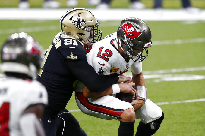 Tampa Bay Buccaneers quarterback Tom Brady (12) is sacked by New Orleans Saints defensive end Trey Hendrickson (91) in the first half of an NFL football game in New Orleans, Sunday, Sept. 13, 2020. (AP Photo/Butch Dill)