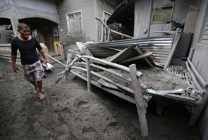 A resident looks at a structure that was damaged from volcanic ash at Laurel, Batangas province, southern Philippines on Tuesday, Jan. 14, 2020. Taal volcano is spewing ash half a mile high and trembling with earthquakes constantly as thousands of people flee villages darkened and blanketed by heavy ash. (AP Photo/Aaron Favila)