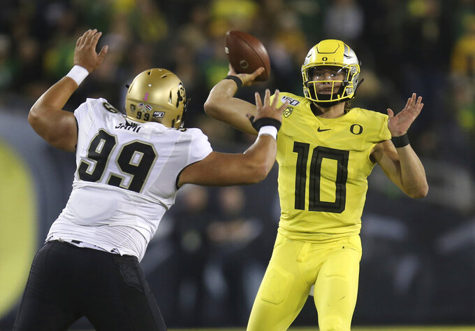 Colorado's Jalen Sami, left, rushes Oregon's Justin Herbert during the first quarter of an NCAA college football game Friday, Oct. 11, 2019, in Eugene, Ore. (AP Photo/Chris Pietsch)