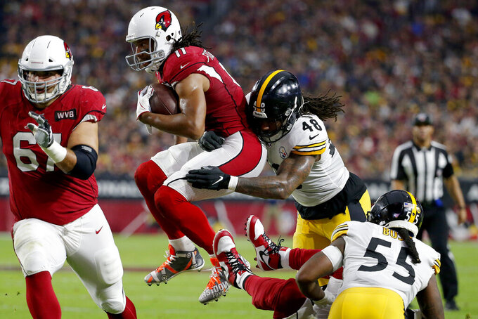 Arizona Cardinals wide receiver Larry Fitzgerald (11) runs as Pittsburgh Steelers outside linebacker Bud Dupree (48) makes the hit during the first half of an NFL football game, Sunday, Dec. 8, 2019, in Glendale, Ariz. (AP Photo/Rick Scuteri)