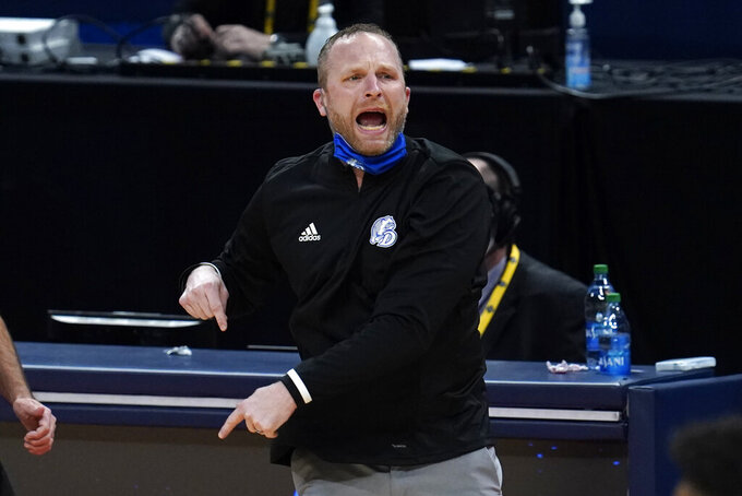 Drake head coach Darian DeVries gives directions against USC during the first half of a men's college basketball game in the first round of the NCAA tournament at Bankers Life Fieldhouse in Indianapolis, Saturday, March 20, 2021. (AP Photo/Paul Sancya)