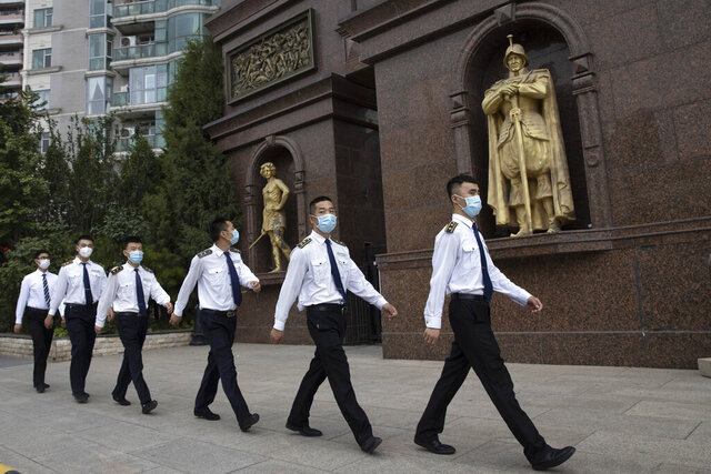 Security guards wearing masks to curb the spread of the coronavirus march past a community with European style statues in Beijing on Monday, June 29, 2020. Even as the world surpassed two sobering coronavirus milestones Sunday -- 500,000 confirmed deaths, 10 million confirmed cases -- and hit another high mark for daily new infections, China on Monday reported a further decline in new confirmed cases. (AP Photo/Ng Han Guan)