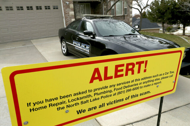 FILE - In this March 21, 2019, file photo, a warning sign and a police officer's vehicle stand out Walt Gilmore's home in North Salt Lake, Utah. A Hawaii man accused of tormenting a Utah family for more than year by using the internet to send more than 500 people to their house for unwanted services including food deliveries, repairs, tow trucks, locksmiths, plumbers and prostitutes pleaded guilty Monday, July 27, 2020, to one count of cyberstalking. Loren Okamura, 44, entered the pleas during a video conference hearing based out of U.S. District Court in Utah that capped off a case that prosecutors called an