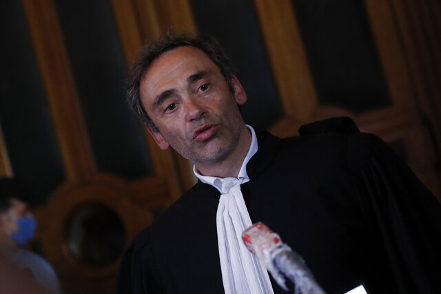 Laurent Bayon, one of Felicien Kabuga's French lawyers, speaks to reporters outside the courtroom, Wednesday, May 20, 2020 in Paris. Felicien Kabuga, one of the most wanted fugitives in Rwanda's 1994 genocide, a wealthy businessman accused of supplying machetes to killers and broadcasting propaganda urging mass slaughter, has been arrested outside Paris last week. (AP Photo/Christophe Ena)