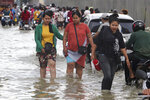 Garment workers make their way to work through the flooded following recent rains at the outskirts of Phnom Penh , Cambodia, Wednesday, Oct. 14, 2020. A Cambodian disaster official said Wednesday that more than 10,000 people have been evacuated to the safety places after the tropical storm hit the country by causing the flash flood. (AP Photo/Heng Sinith)