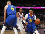 Philadelphia 76ers guard Josh Richardson, center, is hit as he tries to slip past a pick set by Denver Nuggets center Nikola Jokic, left, as Nuggets guard Jamal Murray drives to the rim in the first half of an NBA basketball game Friday, Nov. 8, 2019, in Denver. (AP Photo/David Zalubowski)