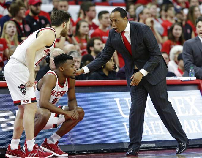 North Carolina State coach Kevin Keatts speaks with Braxton Beverly and Torin Dorn (2) during the first half of the team's NCAA college basketball game against Virginia in Raleigh, N.C., Tuesday, Jan. 29, 2019. (AP Photo/Gerry Broome)