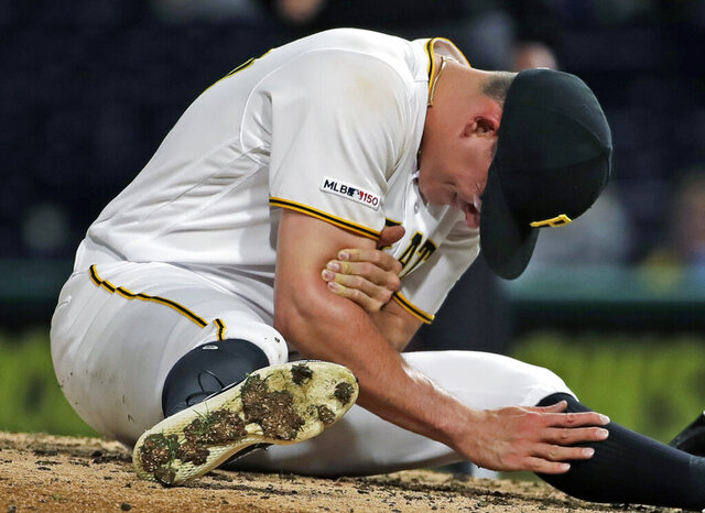 FILE - In this April 22, 2019, file photo, Pittsburgh Pirates relief pitcher Nick Burdi holds his right arm after delivering a pitch during the eighth inning of a baseball game against the Arizona Diamondbacks in Pittsburgh. Burdi is back with the Pirates,  one rib lighter and optimistic his issues with thoracic outlet syndrome are behind him. (AP Photo/Gene J. Puskar, File)