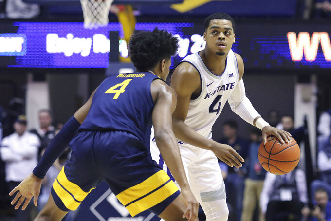 Kansas State guard David Sloan (4) looks to pass the ball as he is defended by West Virginia guard Miles McBride (4) during the first half of an NCAA college basketball game Saturday, Feb. 1, 2020, in Morgantown, W.Va. (AP Photo/Kathleen Batten)