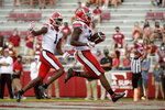 Georgia running back Zamir White (3) celebrates with teammate George Pickens (1) as he scores a touchdown against Arkansas during the second half of an NCAA college football game in Fayetteville, Ark., Saturday, Sept. 26, 2020. No. 5 Georgia has had an off week to prepare for Saturday's game at Kentucky after being shut out in the second half of a 41-24 loss to No. 2 Alabama. With Stetson Bennett expected to retain the starting job at quarterback, the Bulldogs are relying on their running game led by Zamir White to get the offense moving again.(AP Photo/Michael Woods)