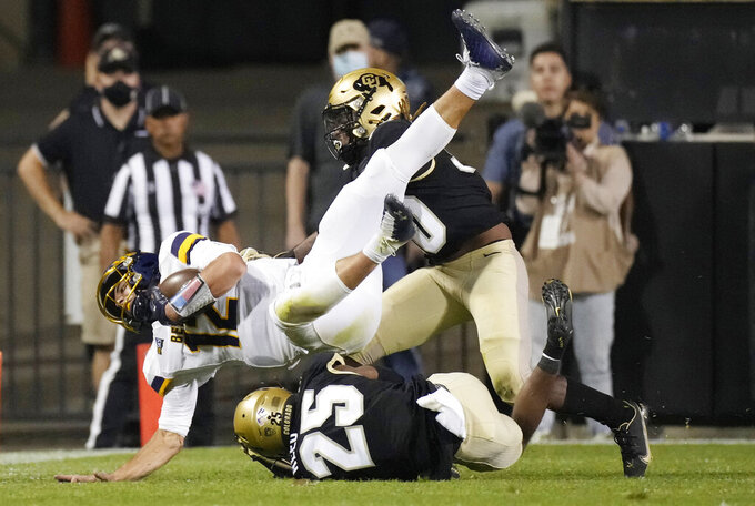 Northern Colorado quarterback Dylan McCaffrey (12) is tackled by Colorado cornerback Nikko Reed, bottom, and safety Curtis Appleton II during the second half of an NCAA college football game Friday, Sept. 3, 2021, in Boulder, Colo. Colorado won 35-7. (AP Photo/David Zalubowski)