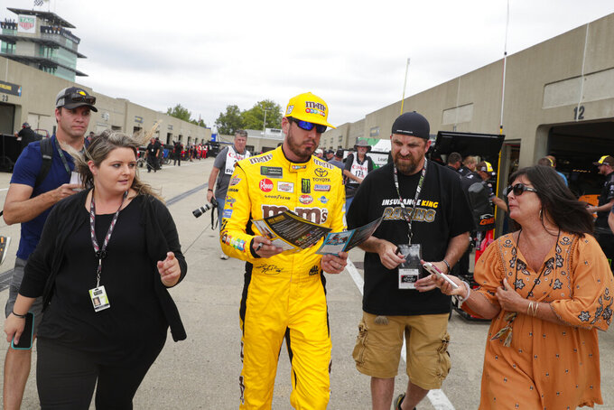 NASCAR Xfinity Series driver Kyle Busch signs autographs as he makes his way through the garage ares during the NASCAR Xfinity auto racing practice at Indianapolis Motor Speedway, Friday, Sept. 6, 2019 in Indianapolis. (AP Photo/Michael Conroy)