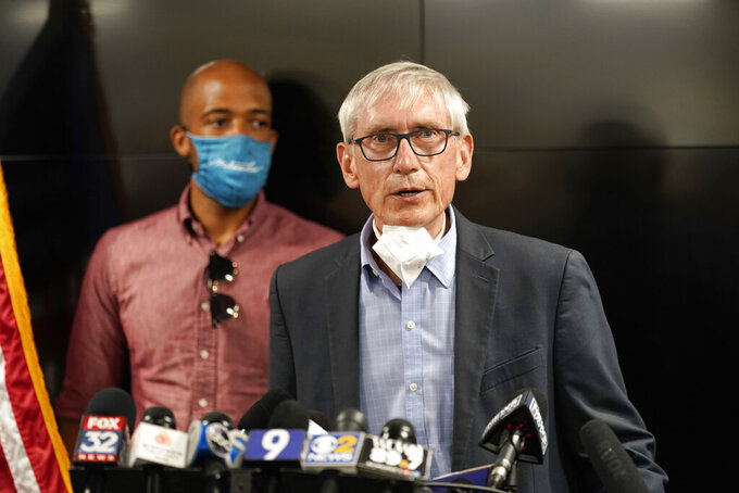 FILE - In this Aug. 27, 2020, file photo, Wisconsin Gov. Tony Evers speaks during a news conference in Kenosha, Wis., as Lt. Gov. Mandela Barnes stands at rear. A federal appeals court ruled Friday, April 9, 2021, that Evers, a Democrat, can exclude members of a conservative think tank from attending press briefings and keep them off his email list sent to other reporters, upholding a ruling from a lower court. (AP Photo/Morry Gash, File)