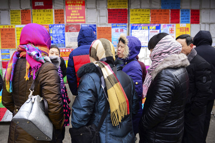 In this Feb. 10, 2019, photo, a group of female job-seekers chat in front of a billboard displaying recruitment leaflets at a labor market in Qingdao in east China's Shandong province. China has announced new measures against gender discrimination that will prevent employers from asking potential female hires questions such as if they are married or have children. (Chinatopix via AP)