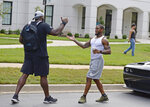 Carolina Panthers tackle Taylor Moton, left, and linebacker Denzel Perryman greet one another at NFL football training camp, Tuesday, July 27, 2021, at Wofford College in Spartanburg, S.C. (Jeff Siner/The Charlotte Observer via AP)