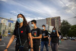 People wearing face masks to help protect against the spread of the coronavirus cross an intersection in Beijing, Tuesday, Aug. 4, 2020. Both mainland China and Hong Kong reported fewer new cases of COVID-19 on Tuesday as strict measures to contain new infections appear to be taking effect. (AP Photo/Mark Schiefelbein)