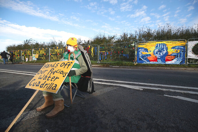 A fracking protester sits outside energy firm Cuadrilla's site in Preston New Road, Little Plumpton, in Lancashire, England, Monday, Oct. 15, 2018. The protesters have said their fight has just