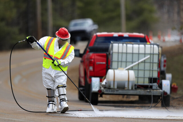 A worker wearing a hazardous material suit hoses debris off a road near the Androscoggin Mill, Thursday, April 16, 2020, in Jay, Maine. A massive explosion at the mill on Wednesday spewed wood fiber and pulping liquor but resulted in no serious injuries. (AP Photo/Robert F. Bukaty)