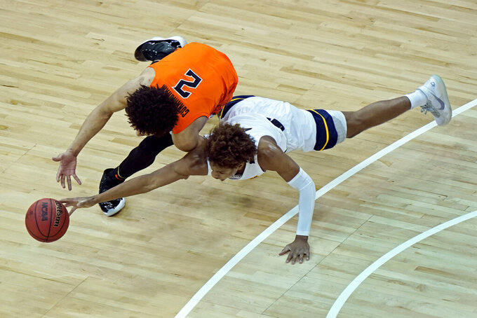 Oklahoma State's Cade Cunningham (2) and West Virginia's Miles McBride chase a loose ball during the first half of an NCAA college basketball game in the second round of the Big 12 Conference tournament in Kansas City, Mo., Thursday, March 11, 2021. (AP Photo/Charlie Riedel)