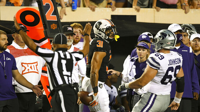 Kansas State offensive lineman Noah Johnson (69) chases Oklahoma State safety Kolby Harvell-Peel (31) out of bounds after Harvell-Peel intercepted a pass during the first half of an NCAA college football game Saturday, Sept. 25, 2021, in Stillwater, Okla. (AP Photo/Brody Schmidt)