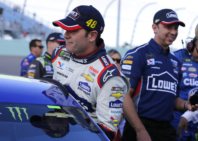 Jimmie Johnson, left, gets into his car before a NASCAR Cup Series Championship auto race at the Homestead-Miami Speedway, Sunday, Nov. 18, 2018, in Homestead, Fla. At right is crew chief Chad Knaus. (AP Photo/Terry Renna)