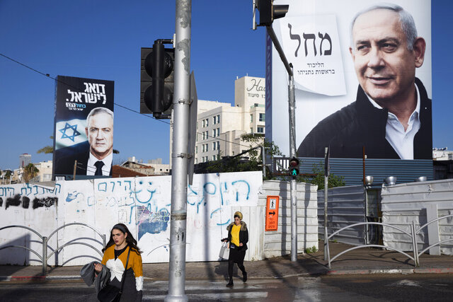 FILE - In this March. 1, 2020 file photo, people walk next to election campaign billboards showing Israeli Prime Minister Benjamin Netanyahu, right, and Benny Gantz, left, in Bnei Brak, Israel. Israel's president on Sunday, April 12, 2020, turned down a request from Blue and White party leader Benny Gantz for a two-week extension to form a new coalition government. The announcement means that Gantz and Netanyahu have a midnight deadline on Monday night to reach a power-sharing deal. If they fail, the country could be forced into a fourth consecutive election in just over a year. (AP Photo/Oded Balilty, File)