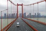FILE - In this Jan. 25, 2020, file photo, an ambulance drives across a nearly empty bridge in Wuhan in central China's Hubei Province. The Chinese city of Wuhan is looking back on a year since it was placed under a 76-day lockdown beginning Jan. 23, 2020.(Chinatopix via AP, File)