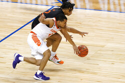 Clemson guard Nick Honor (4) chases a ball with Miami guard Isaiah Wong (2) during the first half of an NCAA college basketball game in the second round of the Atlantic Coast Conference tournament in Greensboro, N.C., Wednesday, March 10, 2021. (AP Photo/Gerry Broome)