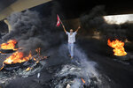 An anti-government protester makes victory sign, as he holds a Lebanese national flag and walks fire of tires that sits to block a road during a protest against government's plans to impose new taxes in Beirut, Lebanon, Friday, Oct. 18, 2019. Demonstrators in Lebanon are blocking major roads across the country in a second day of protests against proposed new taxes, which come amid a severe economic crisis. (AP Photo/Hassan Ammar)