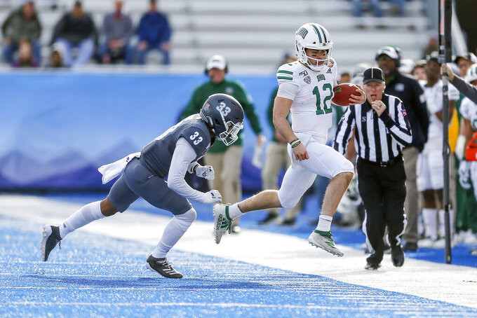Ohio quarterback Nathan Rourke (12) runs out of bounds with the ball as Nevada defensive back JoJuan Claiborne (33) closes in during the first half of the Famous Idaho Potato Bowl NCAA college football game Friday, Jan. 3, 2020, in Boise, Idaho. (AP Photo/Steve Conner)