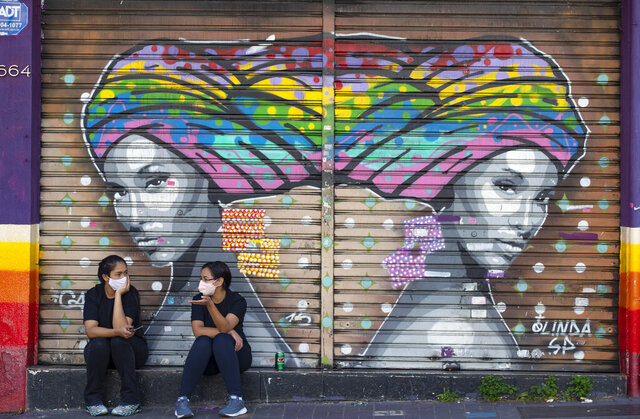 Women talk outside a closed outfit store during a quarantine imposed by the state government to help contain the spread of the new coronavirus in Sao Paulo, Brazil, Monday, June 1, 2020. (AP Photo/Andre Penner)
