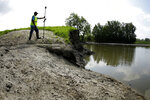 In this Tuesday, Aug. 6, 2019 photo, U.S. Army Corps of Engineers worker Ron Allen uses a GPS tool to survey the extent of damage where a levee failed along the Missouri River near Saline City, Mo. Efforts to fight rising waters may turn out to be only down payments on what is shaping up as a long-term battle against floods, which are forecast to become more frequent and destructive as global temperatures rise. (AP Photo/Charlie Riedel)