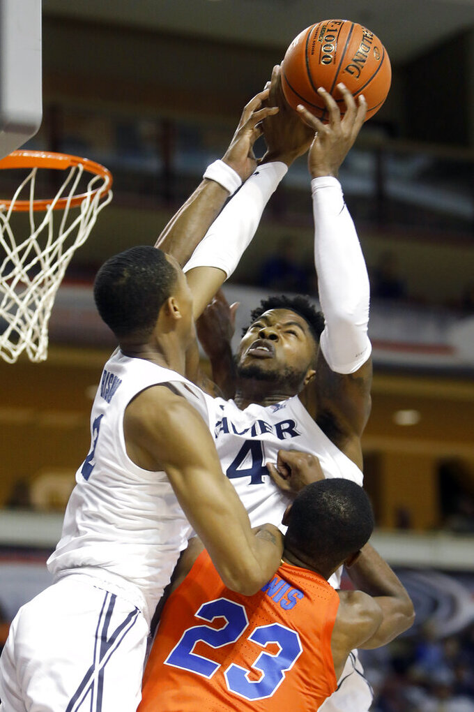 Xavier's Tyrique Jones, center, goes up for a rebound against the defense of Florida's Scottie Lewis in the first half of an NCAA college basketball game during the finals of the Charleston Classic Sunday, Nov. 24, 2019, in Charleston, SC. (AP Photo/Mic Smith)