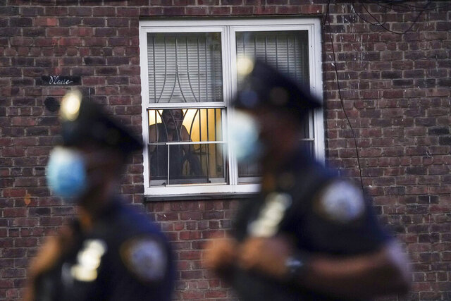 FILE - In this Aug. 18, 2020, file photo, a neighbor watches New York City Police Department officers work a crime scene where several young men were shot and wounded at the Ravenswood Houses in the Queens borough of New York. Heralded as the safest big city in America in recent years, New York City is closing out its bloodiest year in nearly a decade, grappling with a surge in homicides and a pandemic authorities say has helped fuel violence. (AP Photo/John Minchillo, File)