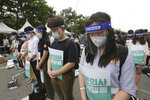 Interns and resident doctors pay their respects to the victims who died after being infected with the coronavirus during a rally against the government medical policy in Seoul, South Korea, Friday, Aug. 7, 2020. Thousands of young doctors in South Korea began a strike Friday in protest of government medical policy, causing concerns about treatment of patients amid the coronavirus pandemic. (AP Photo/Ahn Young-joon)