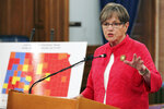 Kansas Gov. Laura Kelly announces that she's imposing a mask mandate for state government workers and visitors to many state buildings, speaking at a news conference, Wednesday, July 28, 2021, at the Statehouse in Topeka, Kan. The large map next to Kelly shows counties with a substantial or high spread of COVID-19 in orange or red, and they are where her new mandate will apply. (AP Photo/John Hanna)