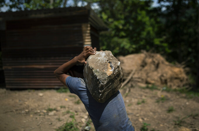 A boy carries a rock at a construction site for new homes for the residents of La Reina, in Mission San Francisco de Asis, Honduras, Saturday, June 26, 2021. Hurricane Eta, then, Hurricane Iota, unleashed rains of biblical proportions in November 2020, causing a mudslide that obliterated the hillside community of La Reina. (AP Photo/Rodrigo Abd)