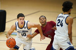 Villanova's Cole Swider (10) dribbles past Saint Joseph's Dahmir Bishop (0) as Jeremiah Robinson-Earl (24) screens during the second half of an NCAA college basketball game, Saturday, Dec. 19, 2020, in Villanova, Pa. (AP Photo/Matt Slocum)