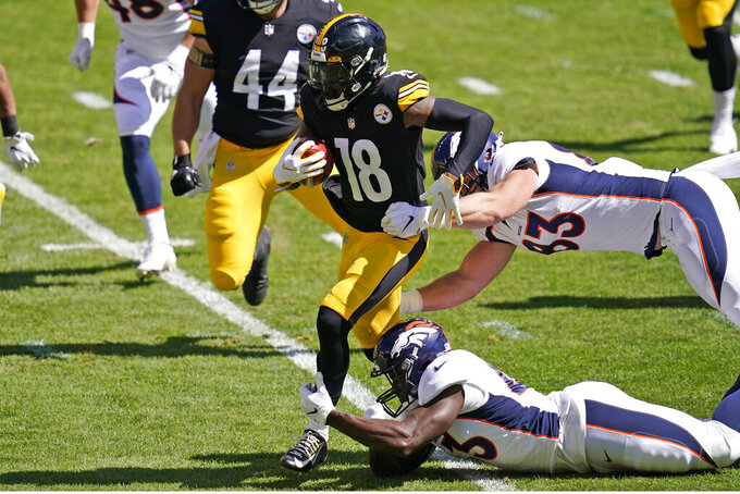 Pittsburgh Steelers wide receiver Diontae Johnson (18) breaks the tackles of Denver Broncos tight end Andrew Beck, top right, and Joe Jones, bottom right, during the first half of an NFL football game, Sunday, Sept. 20, 2020, in Pittsburgh. (AP Photo/Keith Srakocic)