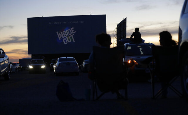 Using social distancing practices, moviegoers watch a show at the Stars and Stripes Drive-In Theater that reopened in New Braunfels, Texas, Friday, May 1, 2020. Texas' stay-at-home orders due to the COVID-19 pandemic have expired and Texas Gov. Greg Abbott has eased restrictions on many businesses that have now opened, including theaters. (AP Photo/Eric Gay)