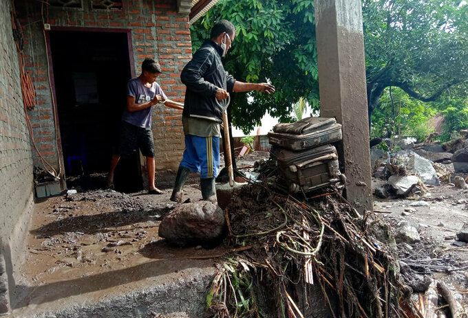 Villagers clean up mud and debris from their house following a flood in Ile Ape, on Lembata Island, East Nusa Tenggara province, Indonesia, Monday, April 5, 2021. Multiple disasters caused by torrential rains in eastern Indonesia and neighboring East Timor have left a number of people dead or missing as rescuers were hampered by damaged bridges and roads and a lack of heavy equipment Monday. (AP Photo/Ricko Wawo)