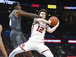 Oklahoma guard Austin Reaves (12) tries to keep the ball away from Mississippi State guard Nick Weatherspoon (0) during the first half of an NCAA college basketball game in Oklahoma City, Saturday, Jan. 25, 2020. (AP Photo/Kyle Phillips)