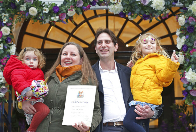 Rebecca Steinfeld and Charles Keidan, with their children Ariel and Eden, pose for the media outside at Kensington and Chelsea Register Office after registering for a civil partnership, in London, Tuesday, Dec. 31, 2019.  England and Wales have marked a new era in which heterosexual couples can choose to have a civil partnership instead of a marriage. The change mandated by Britain's Supreme Court last year took effect Tuesday. The groundbreaking case had been brought by Rebecca Steinfeld and Charles Keidan, who were among the first to form a civil partnership under the new law. (Yui Mok/PA via AP)