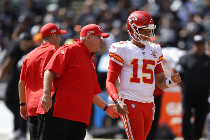 Kansas City Chiefs head coach Andy Reid talks with quarterback Patrick Mahomes (15) before the start of an NFL football game against the Oakland Raiders Sunday, Sept. 15, 2019, in Oakland, Calif. (AP Photo/Ben Margot)