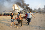 Civilians carry a victim at the explosion scene that hit the seaport, in Beirut Lebanon, Tuesday, Aug. 4, 2020. Massive explosions rocked downtown Beirut on Tuesday, flattening much of the port, damaging buildings and blowing out windows and doors as a giant mushroom cloud rose above the capital. Witnesses saw many people injured by flying glass and debris. (AP Photo/Hussein Malla)