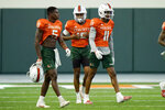 Miami wide receivers Keyshawn Smith (5), Jacolby George (15) and Charleston Rambo (11) take part in NCAA college football practice Tuesday, Aug. 10, 2021, in Coral Gables, Fla. (AP Photo/Lynne Sladky)