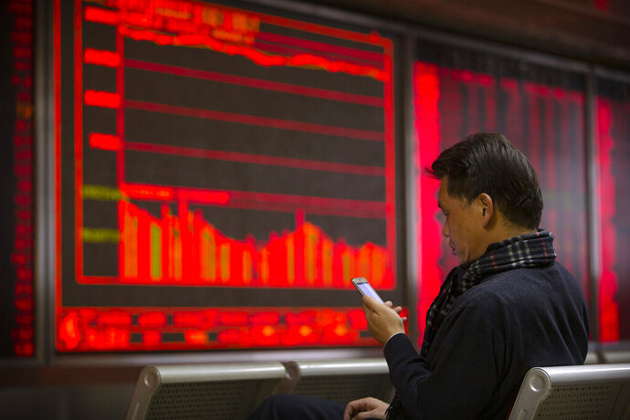 In this Tuesday, Nov. 19, 2019 photo, a Chinese investor uses a smartphone as he monitor stock prices at a brokerage house in Beijing. Shares retreated in Asia on Wednesday after Japan reported its worst monthly decline in exports in three years. (AP Photo/Mark Schiefelbein)