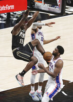 Atlanta Hawks center Clint Capela slams for two points over Philadelphia 76ers defenders Joel Embiid, right, and Tobias Harris on a lob pass from Hawks' Trae Young during the fourth quarter of Game 4 of a second-round NBA basketball playoff series on Monday, June 14, 2021, in Atlanta. (Curtis Compton/Atlanta Journal-Constitution via AP)