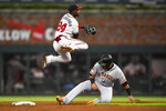 Atlanta Braves second baseman Adeiny Hechavarria (24) throws above San Francisco Giants' Cristhian Adames after forcing him out at second base for a double play on Mauricio Dubon at first base during the fifth inning of a baseball game, Saturday, Sept. 21, 2019, in Atlanta.(AP Photo/John Amis)