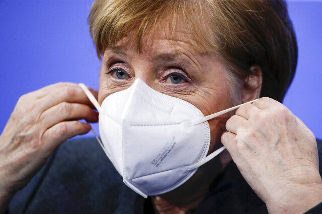 German Chancellor Angela Merkel puts on a face mask after a news conference on further coronavirus measures, at the Chancellery in Berlin, Germany, Tuesday Jan. 19, 2021. (Hannibal Hanschke/Pool via AP)